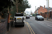 Road sweeper sweeps up leaves from the pavement as other vehicles pass on the road in Kings Heath, Birmingham, United Kingdom.