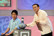 """A presenter examines a participant's  vase on the set of """"Collector's World,"""" a Beijing Television game show. Participants bring their antiques to be appraised by experts and if the articles are deemed to be fakes they are smashed with a golden hammer. The show plays on the country's turbulent modern history, and on the widespread fear of being deceived in a country where everything from DVDs to drugs can be faked."""