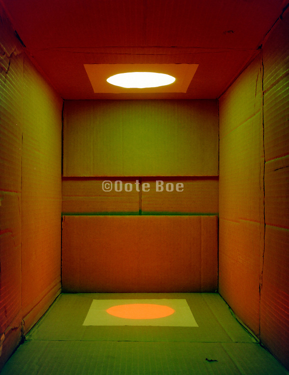 cardboard box with a mixture of red and green light shining in it