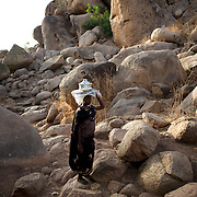 A Nuba woman passes by carrying a pot of food in the mountains outside Buram village in South Kordofan's Nuba Mountains.