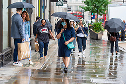 © Licensed to London News Pictures. 27/07/2021. LONDON, UK.  People out shopping during a rain shower in Regent Street.  According to new analyis by Huq Industries, a mobility research business, the UK's Covid app 'pingdemic' is leading to a significant slowdown in people both moving around and visiting shops. Across the UK as a whole in July, average retail footfall has fallen by 2.83% and mobility by 5.5%.  Photo credit: Stephen Chung/LNP