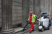 A corporation of London street cleaner with contactor Amey plc, hoovers litter beneath pillars of the Bank of England. Pointing the hose nozzle on the ground where cigarette stubs have been dropped near a bus stop - and outside this famous financial landmark on Threadneedle Street in the City of London, the capital's financial heart. The vehicle is a French-made Diabolo Electrique, used by cleaning companies for street and floor cleaning duties. Amey provides waste collection and street cleansing services providing a commercial waste service on behalf of the City of London as well as a comprehensive fleet management and maintenance service to the council and City of London Police.