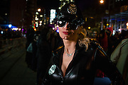 New York, NY - 31 October 2016. A woman costumed as a biker / cop, in leather jacket, a police badge on her jacket and another on her hat, and a handcuff necklace,  in the Greenwich Village Halloween Parade.