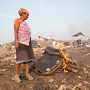 A woman burns old luggages to collects metal in it. Located next to a lake, a visit to one of the main garbage dump in Kolkata. With 15 millions population in 2019 and growing, the city of Calcutta is a typical case of expansion through uncontrolled urbanization.