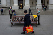 A wet Paint sign and a passing elderly lady, on 16th February 2017, outside Royal Exchange and the WW1 memorial, in the City of London, England.