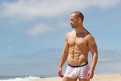 man in wet underwear at the beach