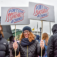 """During the rally before the march, a woman holds two signs, one reading: """"Don't give white supremacy a chance,"""" and the other: """"Don't give bigotry a chance."""" Each sign shows an artistic outline of President Trump's profile."""