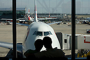 "Honeymooners cuddle in front of their Boeing 747-400 that will soon take them on a round-the-world adventure, leaving from Heathrow Airport's Terminal 5B. The couple are seen as silhouettes against the natural light of the large plate glass windows. As the aircraft is readied and before the flight's air travellers are called to the departure gate, the young man and woman put their heads imagining what new things they will see as their airliner is about to transport them to experience new cultures and possibly a new life. In the background, we see other jets that are parked in their respective jetties across the main movement area, the apron. From writer Alain de Botton's book project ""A Week at the Airport: A Heathrow Diary"" (2009). ."