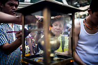 A woman lights incense at the Erawan Shrine in downtown Bangkok, Thailand.