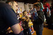 David Snavely of Milpitas Fire Station 4 helps brothers Edgar Mireles, 5 (right), and Jhonefe, 3, select toys for Christmas during a Milpitas Fire Department toy drive at Genesis United Methodist Church in Milpitas, California, on December 21, 2013. (Stan Olszewski/SOSKIphoto)