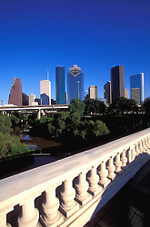 Daytime view of Houston, Texas skyline with Buffalo Bayou and Sabine Bridge in foreground.