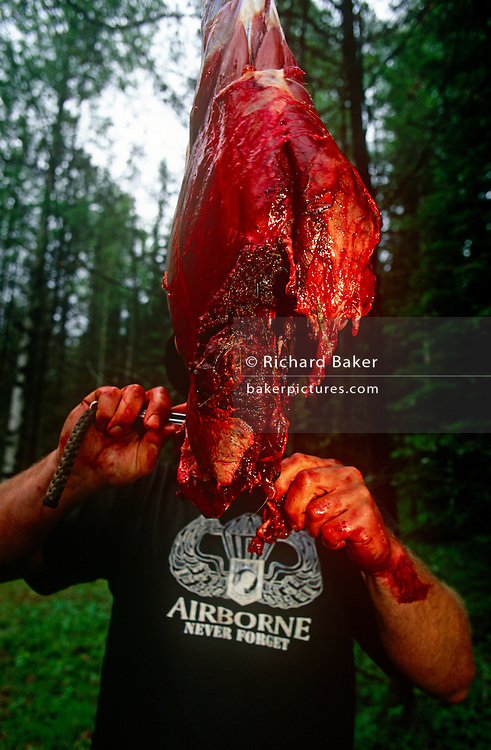 Using a bloodied knife and hand, an instructor of a special US Air Force (USAF) survival course who has butchered roadkill deer...Near their facility at Fairchild AFB, Spokane, Washington State, the man teaches escape and evasion techniques to visiting air crew whose flying careers depend on passing this rigorous week of survival instruction. Should they be downed in hostile territory for example, they will need every skill learned here to survive possibly weeks being hunted in the wilderness so trapping and preparing fresh meat for human consumption is important for survival. Here the teachers stand around the venison which is strung up on a branch, its intestines and organs already removed by a hunting knife.