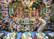 WATFORD HERTFORDSHIRE: A Pujari tends to some of the 4,000 flowers surrounding the deities at the Altar. Over 55,000 pilgrims and guests visit the Largest Hindu Festival in Europe at Bhaktivedanta Manor Krishna Temple near Watford on Sunday 5th September to celebrate Janmashtami the birth of Lord Krishna. The Manor was donated to the Hare Krishna Movement in the early 1970s by former Beatle George Harrison. 03 SEPT 2010. STEPHEN SIMPSON ..
