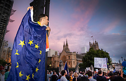 © Licensed to London News Pictures. 28/08/2019. London, UK. An anti-Brexit protestor holds an EU flag as he stands on a traffic light outside Parliament. Earlier it emerged that The Queen will be asked by the government to suspend Parliament in the days after MPs return to work in September - a few weeks before the Brexit deadline of October 31st. Photo credit: Peter Macdiarmid/LNP
