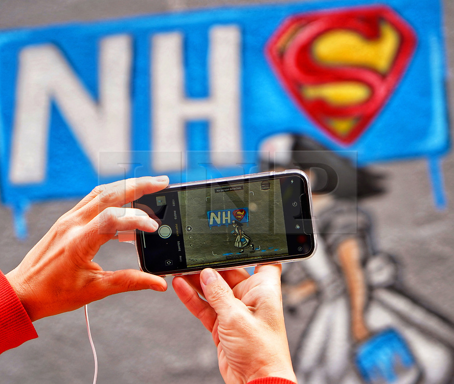 © Licensed to London News Pictures. 03/04/20. Pontefract, UK. An admirer takes a phone photograph of local artist Rachel List's mural  painted on the wall of the Horse Vaults pub in Pontefract, West Yorkshire in support of the NHS., West Yorkshire. Photo credit: Scott Merrylees/LNP