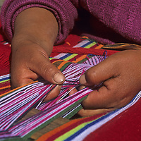 A young woman in Peru's Cordillera Vilcabamba weaves a blanket on a backstrap loom.