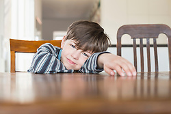 Portrait of boy leaning on wooden table, smiling