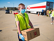 29 MAY 2020 - DES MOINES, IOWA: TRUMAN JAMES, 13, a volunteer, carries a box of produce to a car during a produce distribution in a mall parking lot in Des Moines. The Des Moines Area Religious Council (DMARC) and Capitol City Fruit from Norwalk, IA, gave away 1,800 boxes of fresh produce with a mix of vegetables and fruit. The boxes contain enough produce to feed a family of four for a week. The produce was provided by the USDA Farmers to a Families food program. Because of the COVID-19 pandemic, the unemployment rate in Iowa hit 10.2% in May, the highest unemployment rate ever recorded in Iowa and food insecurity in Iowa is impacting communities throughout the state.         PHOTO BY JACK KURTZ