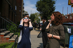 August 21, 2017 - Brooklyn, New York, USA - Residents of the predominantly Orthodox Jewish neighborhood of Borough Park in Brooklyn, look at the solar eclipse through glasses provided by a local optical store. (Credit Image: © Nancy Siesel via ZUMA Wire)
