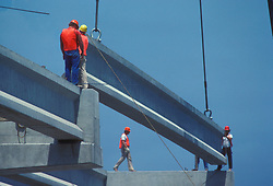 Stock photo of construction workers guide large concrete beams