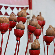 small coconuts inside metal red cups on poles