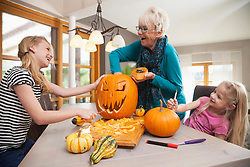 Senior woman carving pumpkin for Halloween with her granddaughters, Bavaria, Germany
