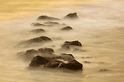 A long camera exposure captures the motion of Pacific Ocean waves crashing over beach rocks at Las Tunas Beach in Malibu, California, in the golden light of the late afternoon.