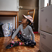 Seven-year-old daughter Keana Nihinsa puts on her shoes to go for lunch, in Hong Kong on March 21, 2019. / Photo: Maria de la Guardia