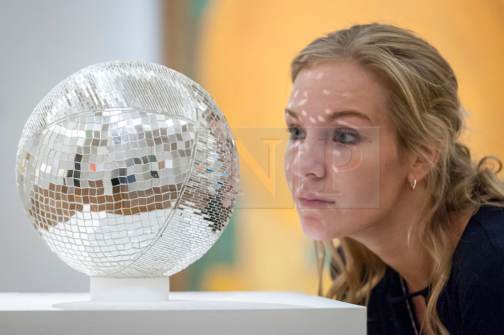 """© Licensed to London News Pictures. 20/10/2017. London, UK. A staff member views """"Mirror Ball"""" by Monit Farmanfarmaian, (GBP35-45k), at a preview of Islamic, Middle Eastern and other artworks which be auctioned at Sotheby's New Bond Street on 24 and 25 October. Photo credit : Stephen Chung/LNP"""
