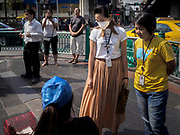 "14 JANUARY 2019 - BANGKOK, THAILAND: A woman wearing dust filter breathing mask talks to a street vender in central Bangkok. Bangkok has been blanketed by heavily polluted air for almost a week. Monday morning, the AQI (Air Quality Index) for Bangkok  was 182, worse than New Delhi, Jakarta, or Beijing. The Saphan Kwai neighborhood of Bangkok recorded an AQI of 370 and the Lat Yao neighborhood recorded an AQI of 403. An AQI above 50 is considered unsafe. Public health officials have warned people to avoid ""unnecessary"" outdoor activities and wear breathing masks to filter out the dust.    PHOTO BY JACK KURTZ"