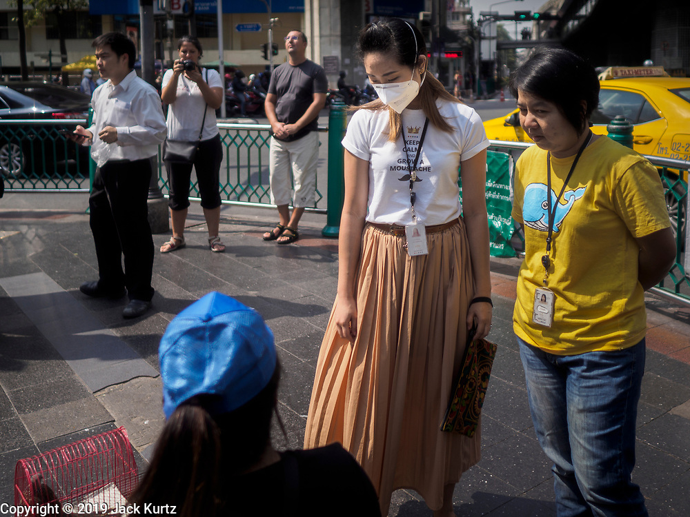 """14 JANUARY 2019 - BANGKOK, THAILAND: A woman wearing dust filter breathing mask talks to a street vender in central Bangkok. Bangkok has been blanketed by heavily polluted air for almost a week. Monday morning, the AQI (Air Quality Index) for Bangkok  was 182, worse than New Delhi, Jakarta, or Beijing. The Saphan Kwai neighborhood of Bangkok recorded an AQI of 370 and the Lat Yao neighborhood recorded an AQI of 403. An AQI above 50 is considered unsafe. Public health officials have warned people to avoid """"unnecessary"""" outdoor activities and wear breathing masks to filter out the dust.    PHOTO BY JACK KURTZ"""