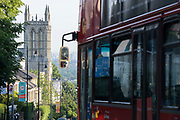 With the London skyline in the far distance, a bus descends towards Christ Church on Gypsy Hill in Crystal Palace, on 16th June 2021, in London, England.