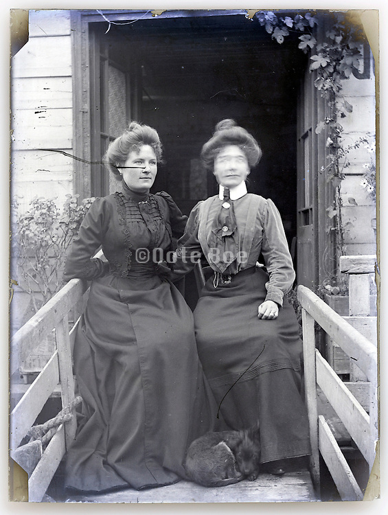 eroding glass plate with two adult women posing on bridge to houseboat Paris 1900s