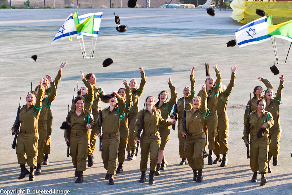 Photography by Debbie Zimelman, Israeli soldiers serving in the IDF toss their hats in the air surrounded by Israeli flags.
