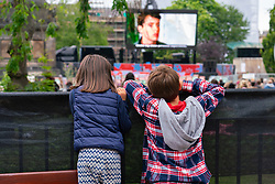 Edinburgh, Scotland, UK. 19th August  2021. Audience watch an outdoor screening of the cult movie Ferris Bueller's Day Off at the  Film Fest in the City outdoor cinema in St Andrew Square. This is one of the events taking place during the Edinburgh International Film Festival in the city. Pic; Young movie goers watch the screening  from over the fence.  Iain Masterton/Alamy Live news.