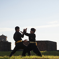 A martial artists in an early morning practice near the Flag Tower of the Citadel Hue, Vietnam.