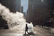 A woman crosses the street past a steam vent in downtown Denver, Colorado.