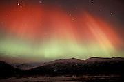 Alaska. Aurora borealis, Northern Lights. Hues of red and green above Knik River Valley near Palmer.