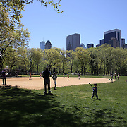 Young baseball players playing Little League in Central Park, Manhattan, New York. USA. Photo Tim Clayton