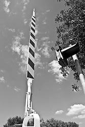 barriera aperta di un passaggio a livello in una stradina di campagna del Salento. Si nota inoltre un semaforo, ulteriore segnale di divieto di attraversare i binari anche e sopratutto in caso di  malfunzionamento della barriera stessa. Reportage che racconta le situazioni che si incontrano durante un viaggio lungo le linee ferroviarie SUD EST nel salento.