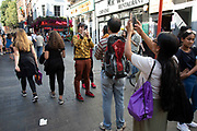 Tourists taking pictures in Chinatown in London, England, United Kingdom. The present Chinatown is in the Soho area occupying the area in and around Gerrard Street. It contains a number of Chinese restaurants, bakeries, supermarkets, souvenir shops, and other Chinese-run businesses and is in itself a major tourist destination.