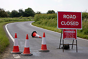 Bollards and a red road closed sign due to Openreach work being carried out on the road between Woodchurch and Appledore on the 24th of June 2021 in Kent, United Kingdom. Even minor work on a country lane can close the entire road causing major diversions to be made.