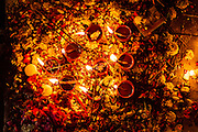 """23rd April 2015, New Delhi, India. Oil lamps and incense sticks burn at a shrine dedicated to Djinn worship in the ruins of Feroz Shah Kotla in New Delhi, India on the 23rd April 2015<br /> <br /> PHOTOGRAPH BY AND COPYRIGHT OF SIMON DE TREY-WHITE a photographer in delhi<br /> + 91 98103 99809. Email: simon@simondetreywhite.com<br /> <br /> People have been coming to Firoz Shah Kotla to leave written notes and offerings for Djinns in the hopes of getting wishes granted since the late 1970's. Jinn, jann or djinn are supernatural creatures in Islamic mythology as well as pre-Islamic Arabian mythology. They are mentioned frequently in the Quran  and other Islamic texts and inhabit an unseen world called Djinnestan. In Islamic theology jinn are said to be creatures with free will, made from smokeless fire by Allah as humans were made of clay, among other things. According to the Quran, jinn have free will, and Iblīs abused this freedom in front of Allah by refusing to bow to Adam when Allah ordered angels and jinn to do so. For disobeying Allah, Iblīs was expelled from Paradise and called """"Shayṭān"""" (Satan).They are usually invisible to humans, but humans do appear clearly to jinn, as they can possess them. Like humans, jinn will also be judged on the Day of Judgment and will be sent to Paradise or Hell according to their deeds. Feroz Shah Tughlaq (r. 1351–88), the Sultan of Delhi, established the fortified city of Ferozabad in 1354, as the new capital of the Delhi Sultanate, and included in it the site of the present Feroz Shah Kotla. Kotla literally means fortress or citadel."""