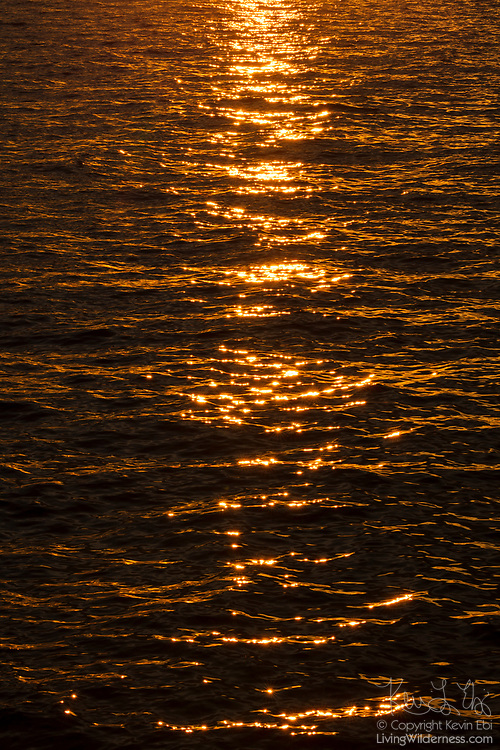 An elongated glint — a line of sunlight reflected across wavy water — stretches across Puget Sound at sunset from the Edmonds, Washington, waterfront.