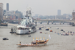 © licensed to London News Pictures. London, UK 27/07/2012. The Olympic Torch on Gloriana go past HMS Belfast as its being carried along River Thames to make the final leg of its epic 8,000 mile journey. Photo credit: Tolga Akmen/LNP