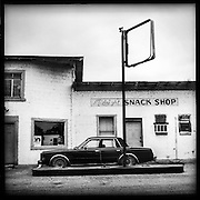 Old vintage car sits in front of an abandoned gas station and snack shop. Midnight, Mississippi