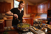USA, Oregon, Eugene, young woman stirring dinner. MR