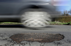 """File photo dated 20/03/18 of a car passing a potholes. Councils should be given a five-year funding settlement to tackle the """"national scandal"""" of potholes on England's local roads, according to MPs."""
