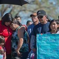 On the left, Aurora Branch wraps her arms around  Chatter Branch and Alta Barnell, right, as they stand will fellow family members of Loreal Tsingine during the Justice for Loreal vigil held in front of the Winslow Police Department Saturday.