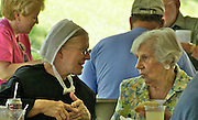 Amish woman and non-Amish friend talk at Amish quilt auction at a fundraiser in Reading, Pennsylvania.